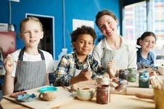 Painting at lesson. Group of intercultural pupils and their teacher in aprons sitting by wooden table in studio of arts and crafts and painting royalty free stock images