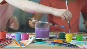 Painting lessons at children art club. Kids putting paintbrush into water glass stock video