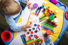 Painting little boy. Little boy painting with gouache on hand, top view Royalty Free Stock Photography
