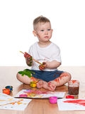 Painting little boy. A little boy paints sitting on the floor Royalty Free Stock Photography