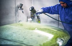 Painting the machine in the chamber with a pneumatic tool on the. Painting the machine with a pneumatic tool in the paint shop Stock Images