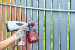 Painting metal fence spray. Man paints a fence with a paint sprayer. painting the fence to protect against corrosion