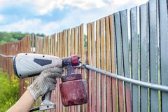 Painting the metal fence with a spray gun, pneumatic sprayer. Protection of metal from paint rust