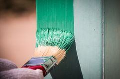 Painting metal surface with a brush. Men is painting metal surface with a brush royalty free stock photography