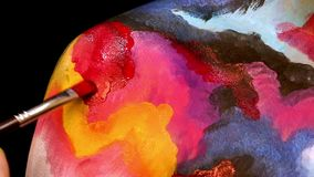 Painting on model's body with brush. Macro footage of art bodypainting. Shallow focus stock footage