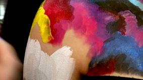 Painting on model's body with brush. Macro footage of art bodypainting. Shallow focus stock video footage