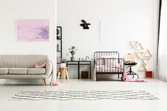 Painting in multifunctional girl`s bedroom. Pink painting above beige sofa in multifunctional girl`s bedroom with moose clock above bed and cabinet stock photos