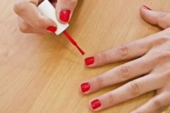Painting nails. Young woman painting her nails red. Great Background Royalty Free Stock Photos