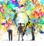Painting a new creative idea. Business person paint together a big colored lightbulb on the wall Stock Photography