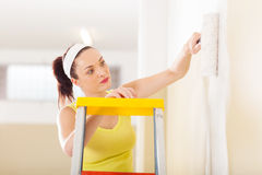 Painting new home. Beautiful young woman painting new home Royalty Free Stock Photos