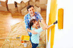 Painting new home. Renovation diy paint couple in new home painting wall Stock Images