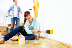 Painting new home. Renovation diy paint couple in new home painting wall Stock Image
