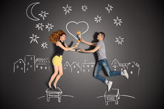 Painting the night sky. Happy valentines love story concept of a romantic couple standing on a stool and painting a heart in the night sky against chalk Stock Images