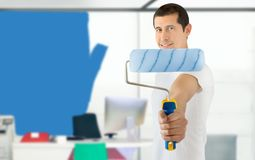 Painting the office. Worker is painting the office in blue and showing the paint roller as concept of reforms at the workplace Royalty Free Stock Photo