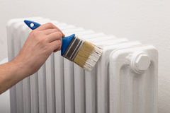 Painting old white radiator with brush Stock Image