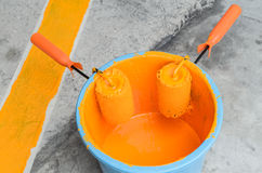 Painting  in a orange color. Paint can with roller brush Stock Photo