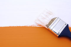 Painting orange surface with white paint Stock Photography