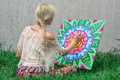 Painting outdoors, a young woman blonde draws a mandala on the nature sitting in the grass royalty free stock photo
