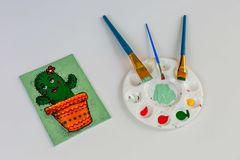 Cute small acrylic painting of a cartoon cactus in a colourful pot stock photography