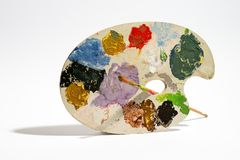 Painting palette with brush on white background. Painting palette with brush and colorful paints against white background Royalty Free Stock Photo
