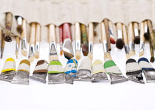 Painting palette and brushes. In focus tubes of color and blurred brushes for painting Royalty Free Stock Image