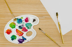 Painting palette, brushes and paper sheets Stock Photography