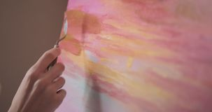 Painting with palette knife. Hand of woman artist painting on canvas using palette knife stock footage