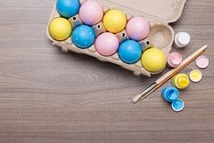 Painting pastel Easter eggs on wooden background stock images