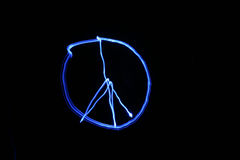 Painting a PEACE sign with light using Time Laps or Bulb exposure. Painting a PEACE sign with a small blue flash light using Time Laps or Bulb exposure in a Stock Photography