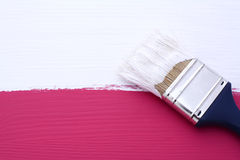 Painting pink surface with white paint Royalty Free Stock Photo