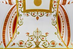 Painting on plaster, flower ornament on the ceiling. Decorative fresco in the interior royalty free stock photography