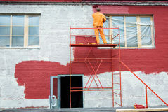 Painting in red. Man painting a brick wall in red royalty free stock image