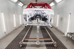 Painting in red and black color of the inside of the frame of the car disassembled after the accident in the workshop for body royalty free stock images