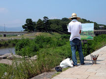 Painting on the riverside. On the Kamogawa riverside,the main river of the Kyoto city,a men is painting Royalty Free Stock Photos