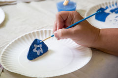 Painting a rock by hand. Blue white star small brush royalty free stock images