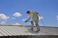 Painting the roof. A trademan uses an airless spray to paint the roof of a building Royalty Free Stock Image