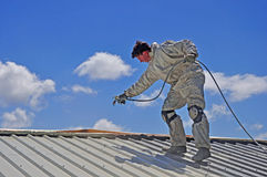 Painting the roof. A trademan uses an airless spray to paint the roof of a building Stock Images