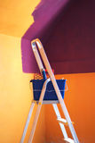 Painting room. Metal ladder and a bucket against wall painted in vivid colors Royalty Free Stock Images
