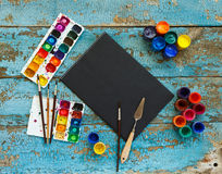 Painting set: brushes, paints, crayons, watercolor, black paper Royalty Free Stock Image