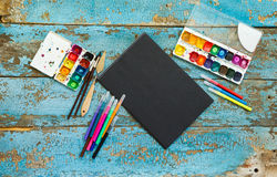 Painting set: brushes, paints, crayons, watercolor, black paper Stock Photo