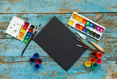 Painting set: brushes, paints, crayons, watercolor, black paper Stock Photography