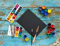 Painting set: brushes, paints, crayons, watercolor, black paper Stock Photos