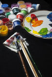 Painting set gouache. Jars with gouache, a set of brushes and a palette with paint Royalty Free Stock Images