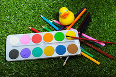 Painting set for young schoolboy. Consisting of yellow rubber ducks, bright colors for drawing and colored pencils Royalty Free Stock Photos