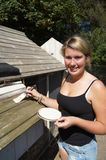 Painting the Shed. Girl applying cream coloured stain to outside shed to weatherproof the wood Royalty Free Stock Images