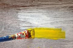 Painting single yellow stripe on wooden background. Details and texture with focus on bristles of paintbrush and the wet paint stock images