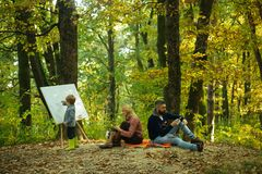 Painting skills. Mom and dad work park while kid painting. Rest and hobby concept. Work and professional occupation. Little son painting picture in nature. Art stock photos