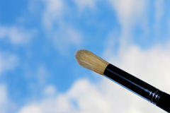 Painting the sky. A paintbrush with tha sky as background stock photography