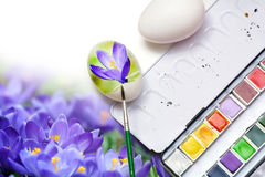 Painting spring flowers on eggs for easter decoration Stock Photos
