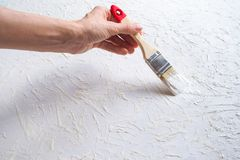Decorating the wall surface with enamel using a brush. stock photo